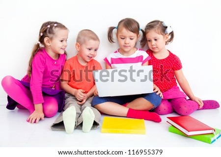 Group of four children working on laptop together