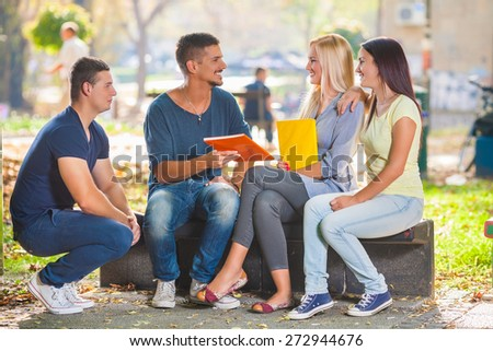 Group of four college students studying together in a park #272944676