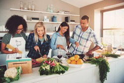 Group of four diverse friends preparing a meal with vegetables and fruit in kitchen for themselves or a culinary class
