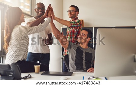 Group of four diverse men and women in casual clothing celebrating an important milestone while relaxing in office near large bright window