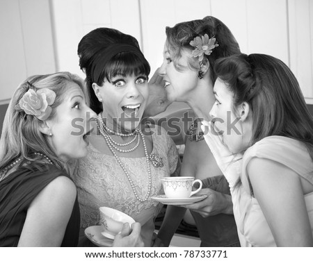 Group of four excited housewives in a kitchen share secrets