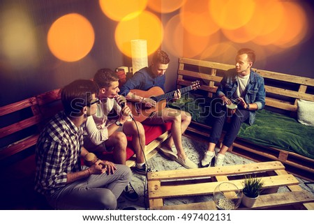 Group of Four Friends Hanging Out in Studio. Guys Singing and Playing Music in Urban Apartment. Toned Photo with Bokeh. #497402131