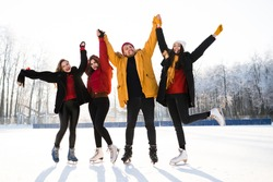Group of four friends have fun in the park while ice skating.