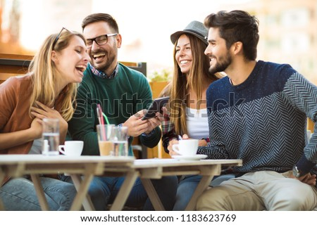 Group of four friends having a coffee together. Two women and two men at cafe talking laughing and enjoying their time using digital tablet. #1183623769