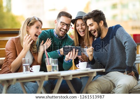 Group of four friends having a coffee together. Two women and two men at cafe talking laughing and enjoying their time using digital tablet. #1261513987