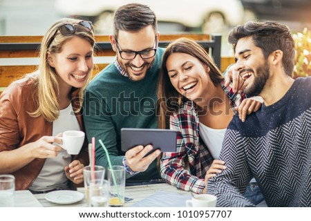 Group of four friends having fun a coffee together. Two women and two men at cafe talking laughing and enjoying their time #1010957707