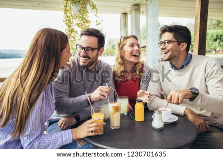Group of four friends having fun a coffee together. Two women and two men at cafe talking laughing and enjoying their time #1230701635