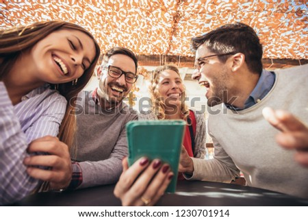 Group of four friends having fun a coffee together. Two women and two men at cafe talking laughing and using smart phone. #1230701914