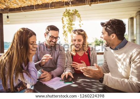 Group of four friends having fun a coffee together. Two women and two men at cafe talking laughing and using smart phone. #1260224398