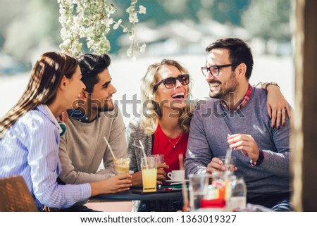 Group of four friends having fun a coffee together. Two women and two men at cafe talking laughing and enjoying their time #1363019327