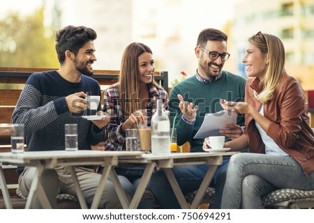 Group of four friends having fun a coffee together. Two women and two men at cafe talking laughing and enjoying their time #750694291
