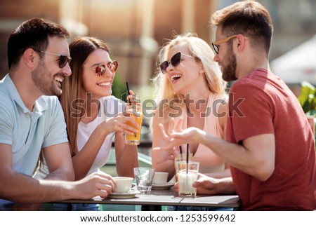 Group of four friends having fun and drink coffee together. Two women and two men at cafe talking ,laughing and enjoying their time #1253599642