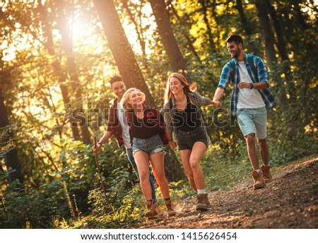 Group of four friends having fun hiking through forest together. #1415626454
