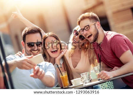 Group of four friends having fun in cafe together. Two women and two men at cafe talking, laughing and enjoying their time. #1293063916