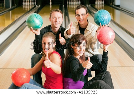 Group of four friends in a bowling alley having fun, holding their bowling balls and showing thumbs up (focus on guys in second row)