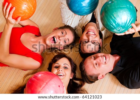 Group of four friends lying in a bowling alley having fun, holding their bowling balls above them