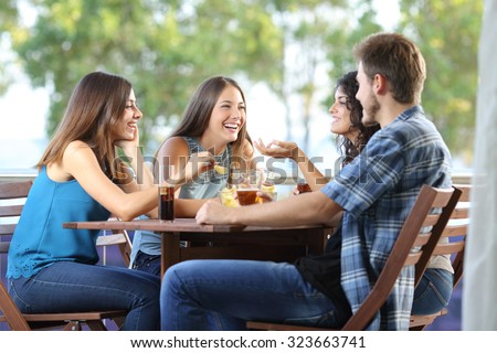 Group of four friends talking and drinking sitting in a terrace at home