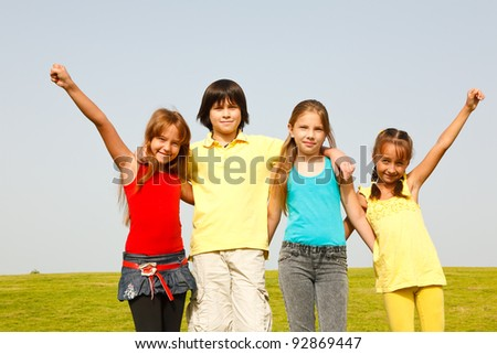 Group of four happy children jumping outdoors.