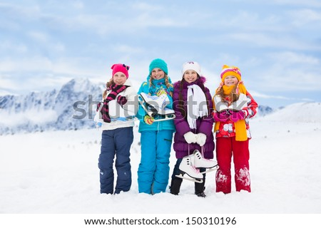 Group of four happy smiling Caucasian girls friends standing outside with ice-skates