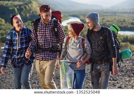 Group of four happy travelers are walking with the map and trying to find out the right way on mountain top at sunset, laughing and talking each other. Tourism and healthy lifestyle concept. #1352525048