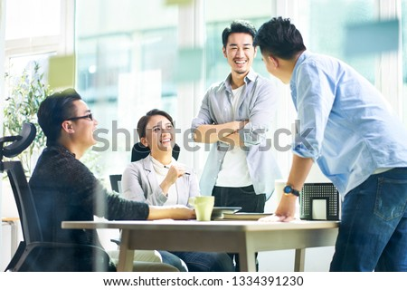 group of four happy young asian corporate people teammates meeting discussing business in office.
