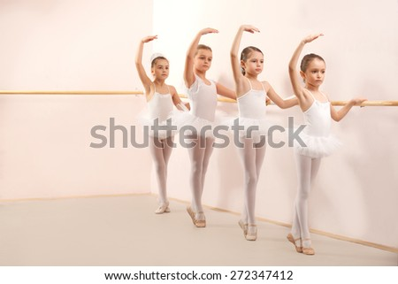 Group of four little ballerinas standing in row and practicing ballet and using stick on the wall. They are good friend and amazing dance performers