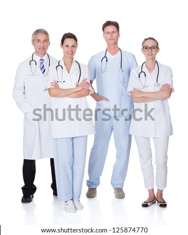 Group of four medical professionals with a male doctor and surgeon and two females doctors on a white studio background - stock photo
