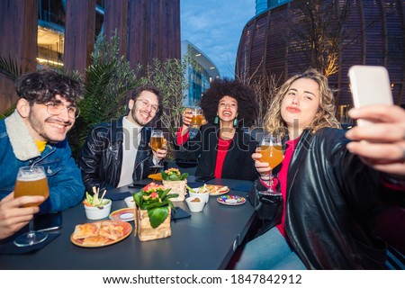 Group of four multiethnic people clubbing making a toast taking selfie celebrating together at bnight sitting pub  Stock photo ©