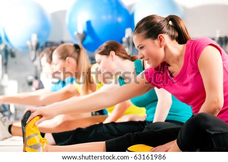 Group of four people in colorful cloths in a gym doing aerobics or warming up with gymnastics and stretching exercises