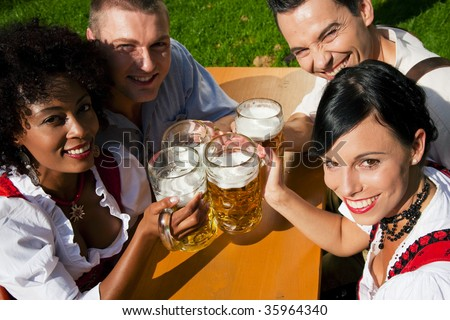 Group of four people in Couple in traditional Bavarian dress, Lederhosen and Dirndl, in a beer garden
