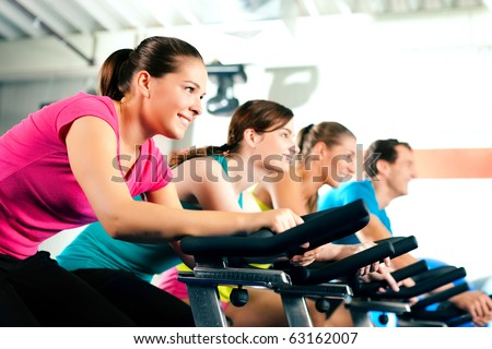 Group of four people in the gym exercising their legs doing cardio training