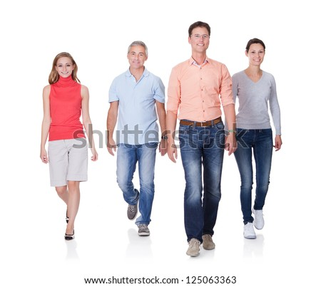 Group of four people walking towards camera. Isolated on white