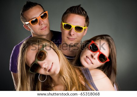 group of four persons with multi colored sunglasses
