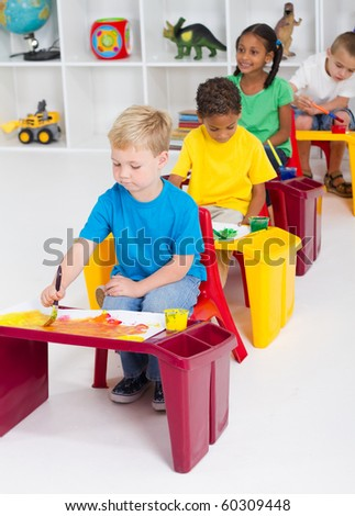 group of four preschool kids in classroom painting picture