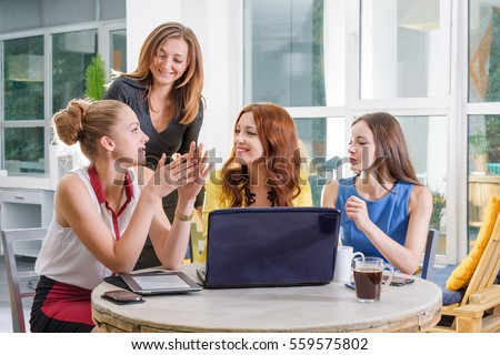 Group of four pretty businesswoman working together with new startup project using laptop computer in modern loft. People and teamwork concept - happy creative team in office. Women in business.