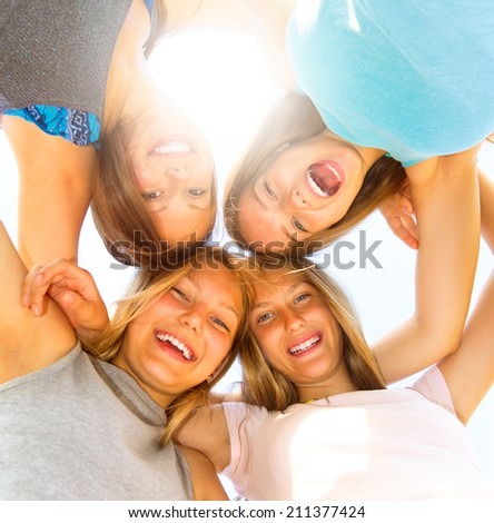 Group of Four Teenage Girls having fun outdoors. Friendship concept. Group of smiling friends staying together, looking at camera and laughing over blue sky. Joyful girlfriends making a huddle #211377424