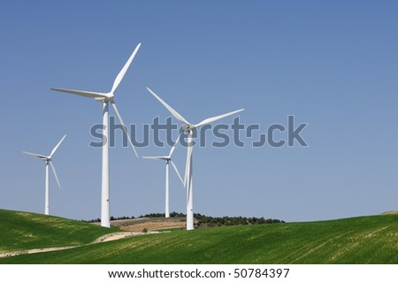 group of four wind turbines on green grass and clear blue sky