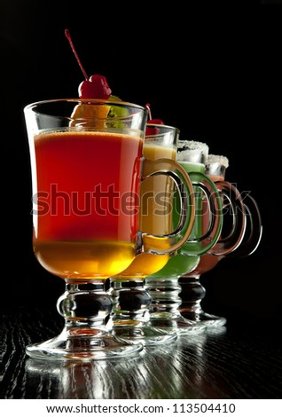 Group of four wine glasses with colored alcoholic cocktails, decorated with fruit and sugar on black bar counter