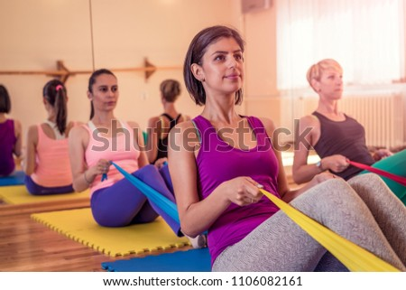 Group of four women doing pilates and stretching exercise with resistance bands in yoga studio. Teamwork, good mood and healthy lifestyle concept. Foto stock ©