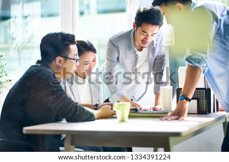 group of four young asian corporate executives meeting in office discussing business in office.