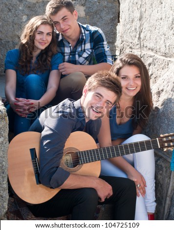 Group of four young happy smiling people with guitar having fun by posing outdoors in spring or summer sitting on the stone staircase.