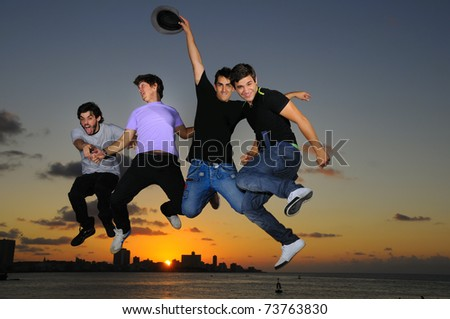 Group of four young males jumping against sunset sky background with happy expression