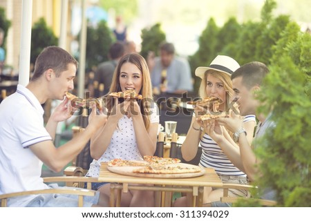 Group of four young people eating pizza in a restaurant