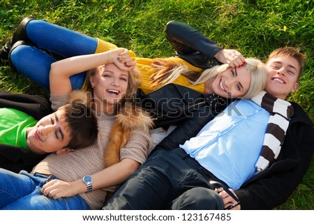 Group of four young people - two couples laying in the grass with smile no their faces