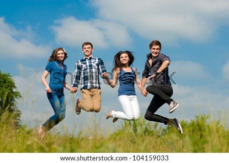 Group of Four Young people two girls & two boys happy smiling in joyful fun jump outdoors in bright sunny day of spring or summer with green field of park or garden and beautiful sky on the background