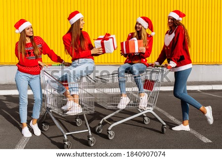 Group of four young women in christmas sweaters and santa claus hats with christmas gifts on carts near shopping mall