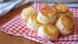 Group of Fresh Homemade butter scones on Checkered tablecloth on wooden table.