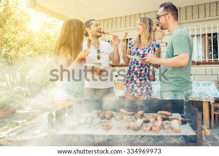 Group of friend having lunch in the backyard. making barbecue outdoor with different kind of meat and vegetables