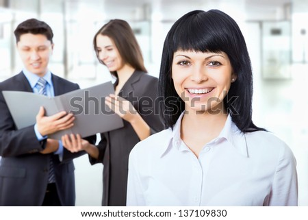 Group of friendly businesspeople with female leader in front