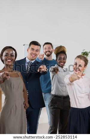 Group of friendly businesspeople with female leader in front pointing at camera